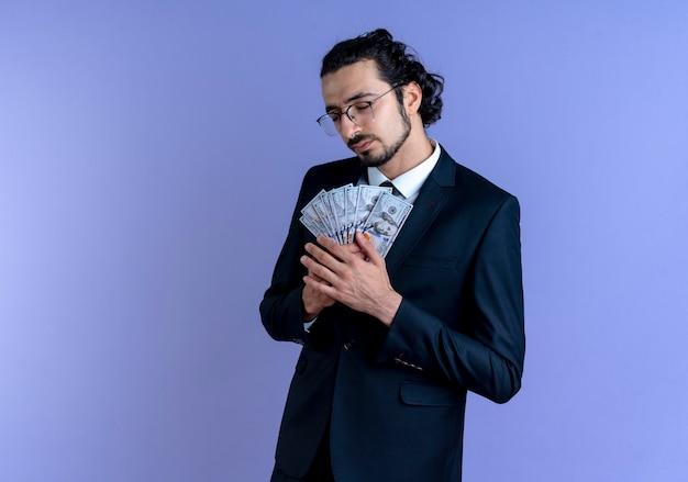 Uomo d'affari in abito nero e occhiali in possesso di contanti sentirsi grato con gli occhi chiusi in piedi sopra la parete blu