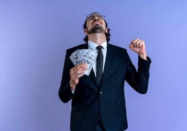 Uomo di affari in vestito nero e vetri che tengono il pugno di serraggio felice ed eccitato dei contanti che sta sopra la parete blu