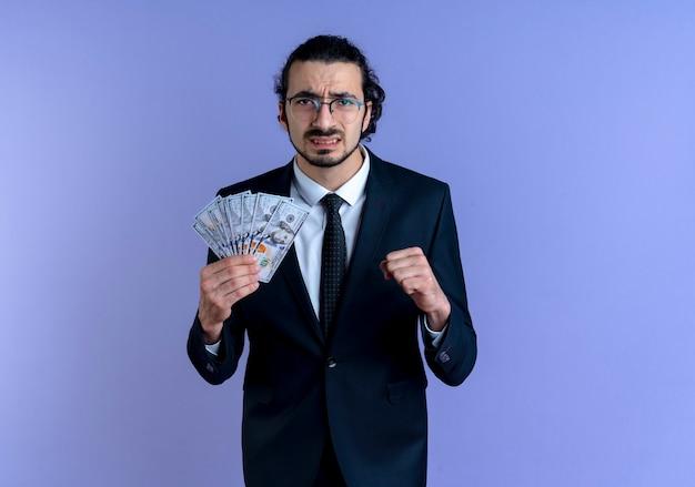 Uomo d'affari in abito nero e occhiali in possesso di contanti guardando il pugno di serraggio anteriore con espressione infastidita in piedi sopra la parete blu