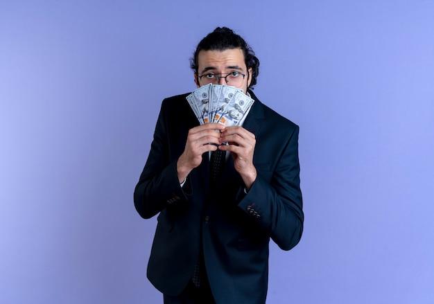 Uomo d'affari in abito nero e occhiali in possesso di contanti guardando in avanti confuso in piedi sopra la parete blu
