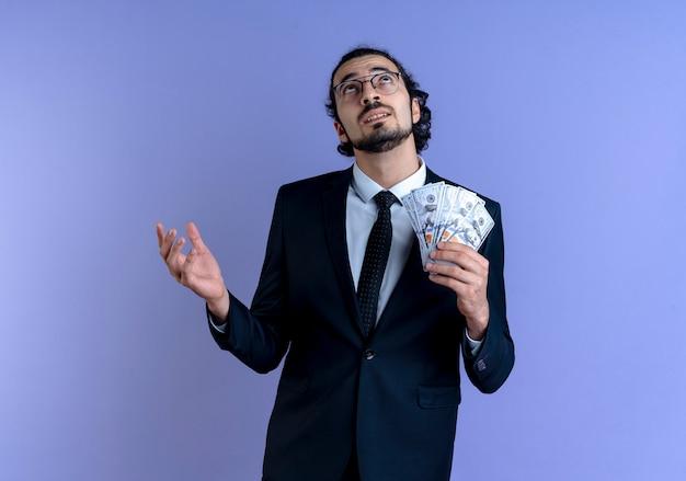 Uomo di affari in vestito nero e occhiali che tengono contanti che cercano in piedi perplesso sopra la parete blu