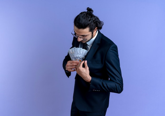 Uomo di affari in vestito nero e occhiali che tengono contanti che mettono soldi nella sua tasca della tuta in piedi sopra la parete blu