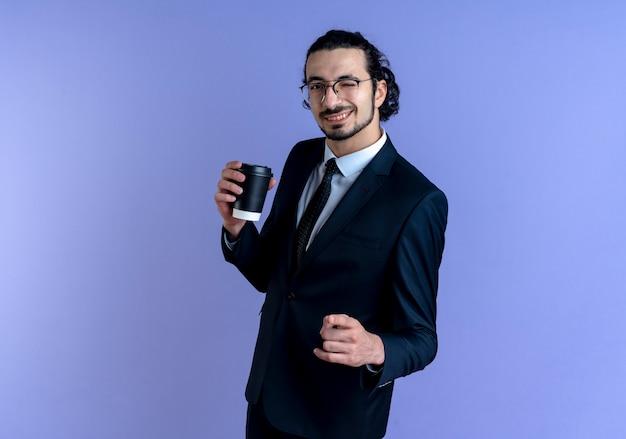 Uomo di affari in vestito nero e vetri che tengono il pugno di serraggio della tazza di caffè felice e positivo sorridente e ammiccante che sta sopra la parete blu