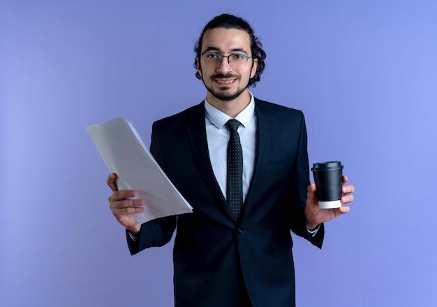 Uomo di affari in vestito nero e occhiali che tengono tazza di caffè e documenti che guardano al fronte sorridendo allegramente in piedi sopra la parete blu