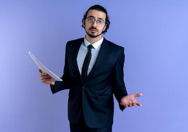Uomo d'affari in abito nero e bicchieri in possesso di documenti guardando in avanti confuso in piedi sopra la parete blu