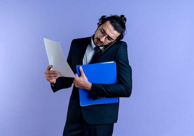 Uomo d'affari in abito nero e occhiali che tengono cartella e documenti mentre si parla al telefono cellulare in piedi sopra la parete blu