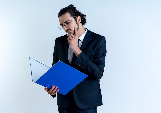 Uomo d'affari in abito nero e occhiali tenendo la cartella, guardandolo perplesso in piedi sopra il muro bianco