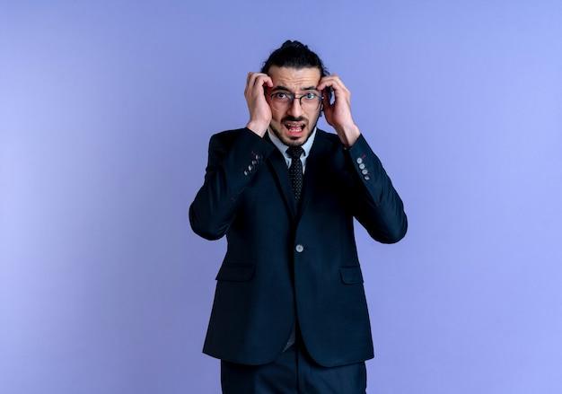 Uomo d'affari in abito nero e occhiali tenendo la testa con le mani guardando in avanti con espressione di paura in piedi sopra la parete blu