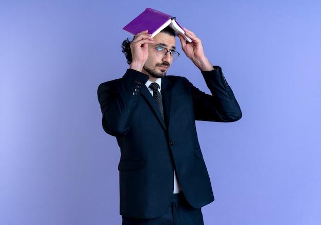 Uomo di affari in vestito nero e occhiali che tengono il taccuino sopra la sua testa che sembra stanco e annoiato in piedi sopra la parete blu