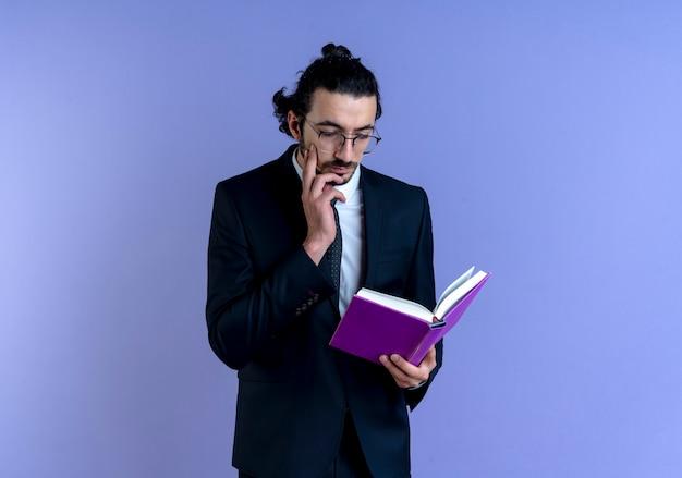 Uomo di affari in vestito nero e occhiali che tengono taccuino che lo esamina con la faccia seria che sta sopra la parete blu