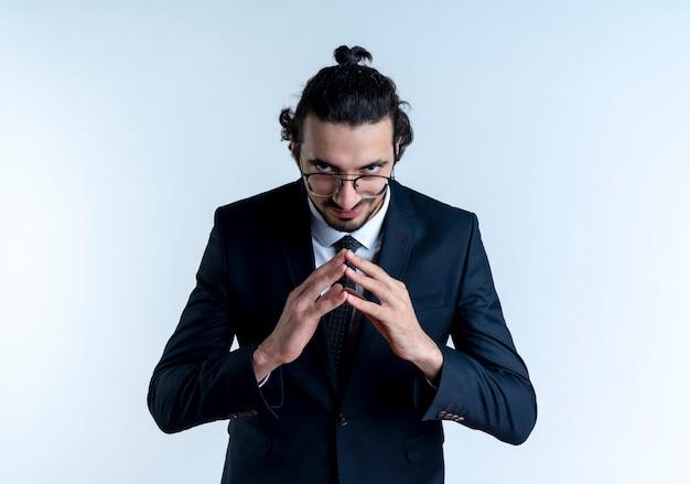 Uomo d'affari in abito nero e occhiali tenendo le palme insieme guardando in avanti furbescamente in attesa di qualcosa in piedi sopra il muro bianco