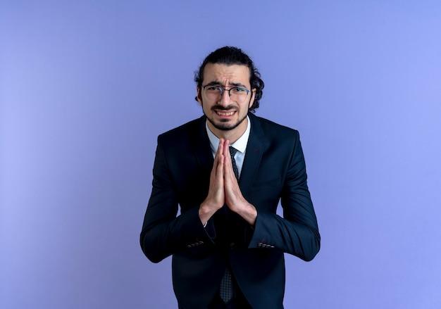 Uomo d'affari in abito nero e occhiali che tengono le palme insieme pregando e implorando con espressione di speranza in piedi sopra la parete blu