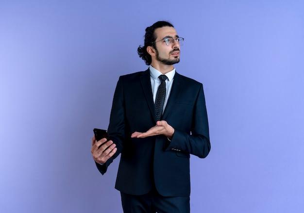 Uomo di affari in vestito nero e occhiali che tengono smartphone che sembra confuso in piedi sopra la parete blu