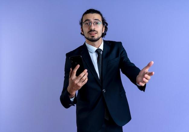 Uomo d'affari in abito nero e occhiali che tiene smartphone guardando in avanti confuso con il braccio fuori in piedi sopra la parete blu