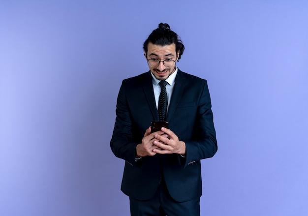 Uomo d'affari in abito nero e occhiali che tiene smartphone guardando sorpreso e stupito in piedi sopra la parete blu