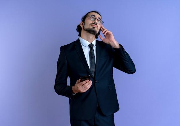 Uomo di affari in vestito nero e occhiali che tengono smartphone che osserva in su in piedi perplesso sopra la parete blu
