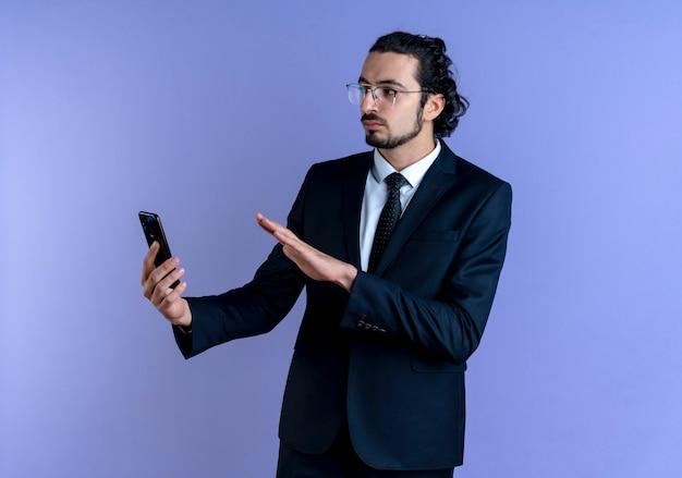 Uomo di affari in vestito nero e occhiali che tengono smartphone che fa gesto di difesa con faccia seria in piedi sopra la parete blu