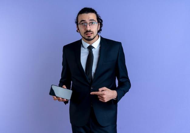 Uomo di affari in vestito nero e occhiali che tiene smartphone che punta con il dito indice ad esso guardando in avanti confuso in piedi sopra la parete blu