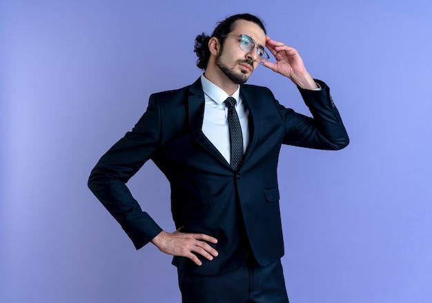 Uomo d'affari in abito nero e occhiali guardando da parte confuso con la mano sulla sua testa in piedi sopra la parete blu