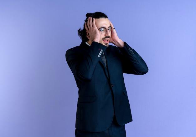 Uomo d'affari in abito nero e occhiali che osserva da parte tenendo la testa con le mani confuse e molto ansiose in piedi oltre il muro blu