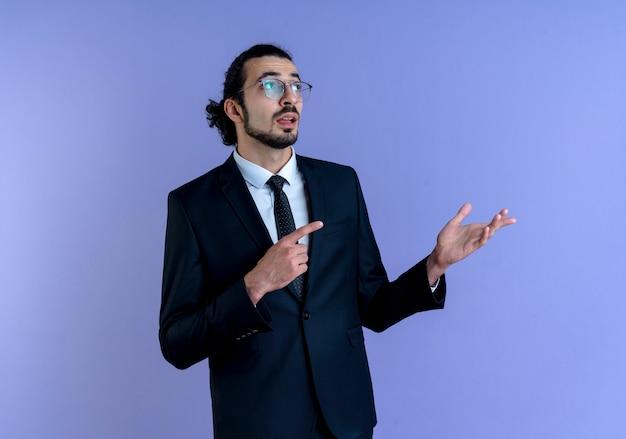 Uomo di affari in vestito nero e occhiali che osserva da parte che indica con il dito indice al lato che presenta con il braccio della sua mano che sta sopra la parete blu