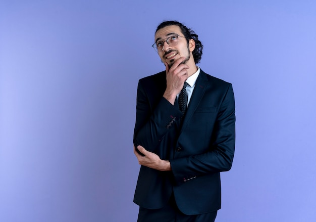 Uomo d'affari in abito nero e occhiali guardando da parte con la mano sul mento sorridendo e pensando in piedi sopra la parete blu