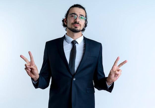 Uomo d'affari in abito nero e occhiali guardando fiducioso che mostra il segno di vittoria con entrambe le mani in piedi sul muro bianco