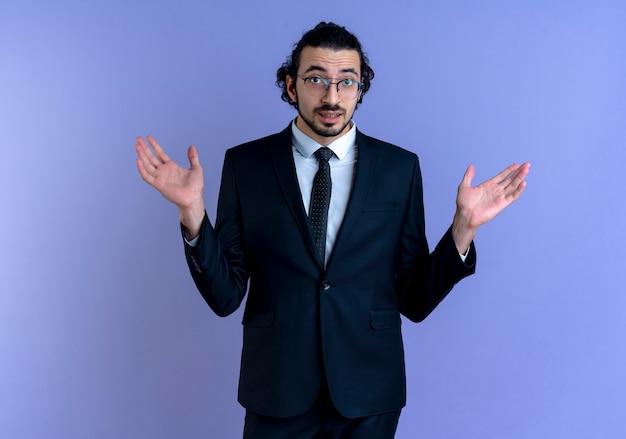 Uomo d'affari in abito nero e occhiali guardando confuso scrollare le spalle non avendo risposta in piedi oltre il muro blu