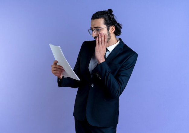 Business man in black suit and glasses looking at documents worried with hand on his face standing over blue wall