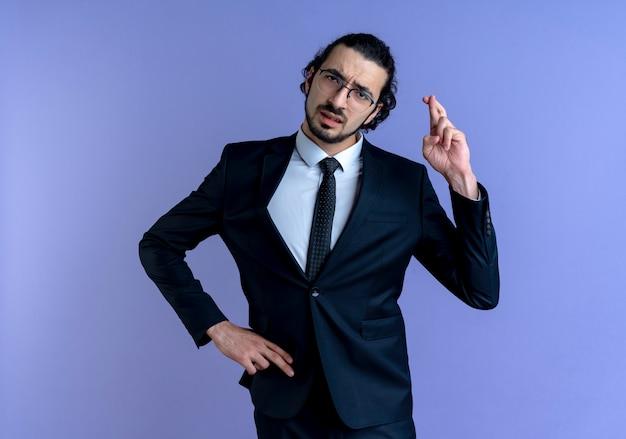 Uomo d'affari in abito nero e occhiali che guardano in avanti rendendo il desiderio incrociando le dita in piedi sulla parete blu
