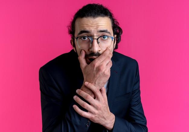 Uomo d'affari in abito nero e occhiali guardando la bocca di copertura scioccata anteriore con la mano in piedi sul muro rosa