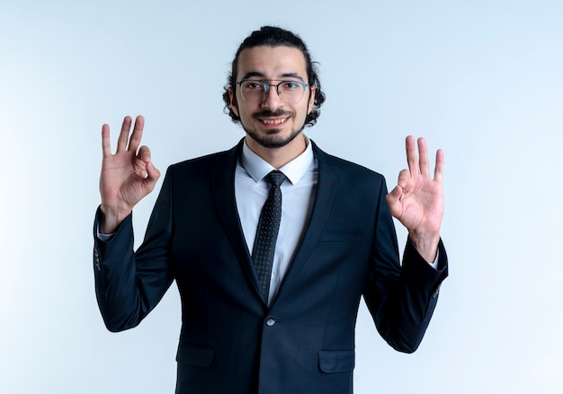Business man in black suit and glasses looking to the front showing ok sign with both hands smiling standing over white wall