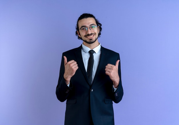 Business man in black suit and glasses looking to the front smiling cheerfully showing thumbs up standing over blue wall