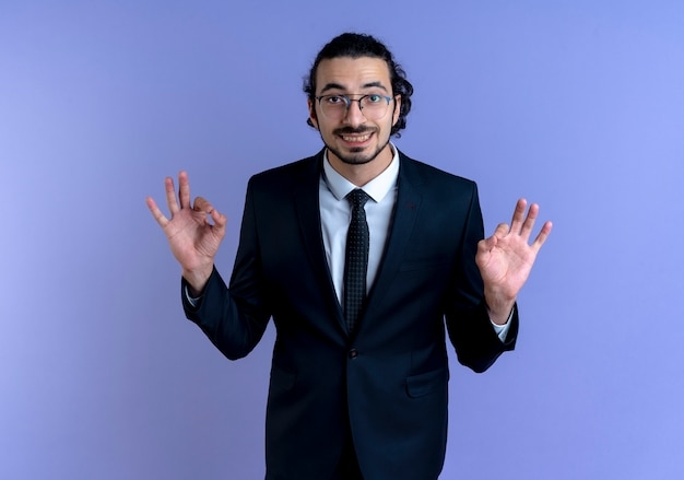 Business man in black suit and glasses looking to the front smiling making meditation gesture with fingers standing over blue wall