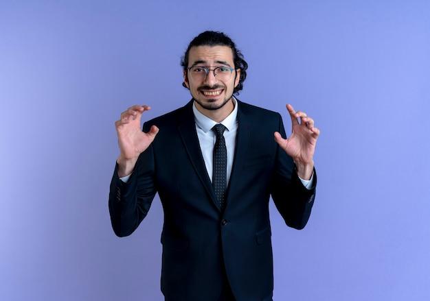 Uomo d'affari in abito nero e occhiali guardando in avanti minacciando con le mani facendo gesto di artigli come gatto in piedi sopra la parete blu