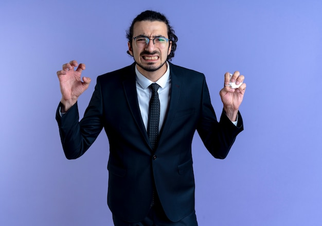 Business man in black suit and glasses looking to the front wirh raised hands with annoyed expression disappointed standing over blue wall