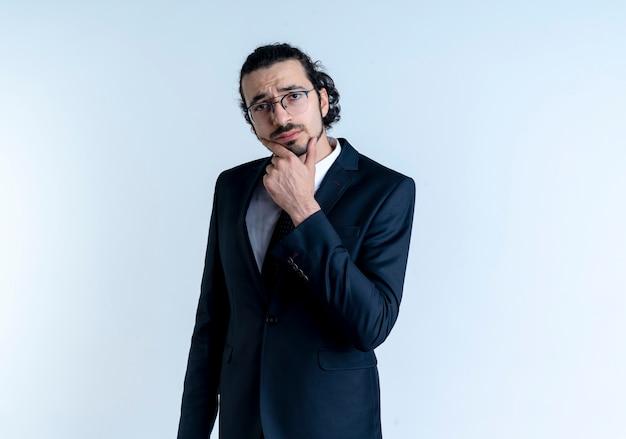 Uomo d'affari in abito nero e occhiali guardando in avanti con la mano sul mento pensando in piedi sopra il muro bianco