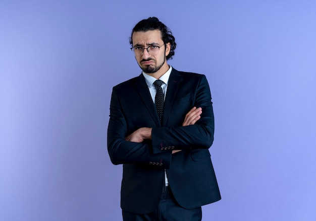 Business man in black suit and glasses looking to the front with sad expression on face standing over blue wall