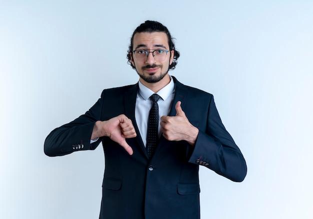 Uomo d'affari in abito nero e occhiali guardando in avanti con un sorriso scettico che mostra i pollici in su e in giù in piedi sul muro bianco