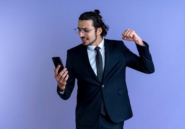 Business man in black suit and glasses looking at his smartphone raising fist excited and angry standing over blue wall