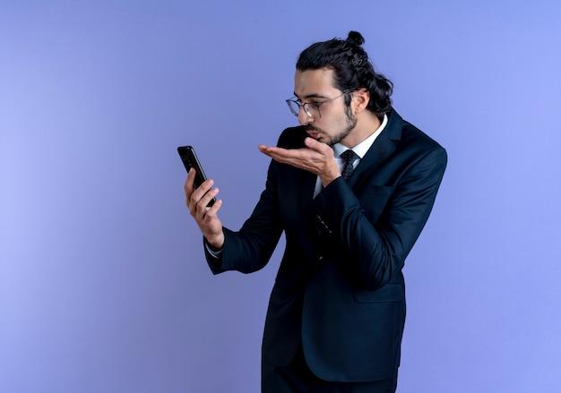 Uomo d'affari in abito nero e occhiali guardando il suo schermo dello smartphone in videochiamata che soffia un bacio in piedi sopra la parete blu