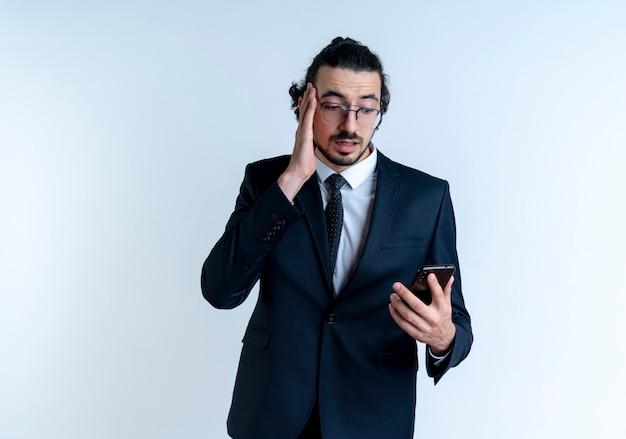Uomo d'affari in abito nero e occhiali guardando lo schermo del suo smartphone confuso e molto ansioso in piedi sopra il muro bianco