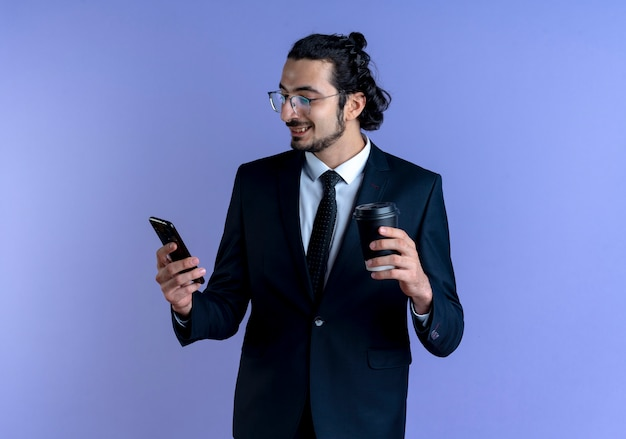 Uomo d'affari in abito nero e occhiali guardando lo schermo del suo smartphone tenendo la tazza di caffè sorridente in piedi sopra la parete blu