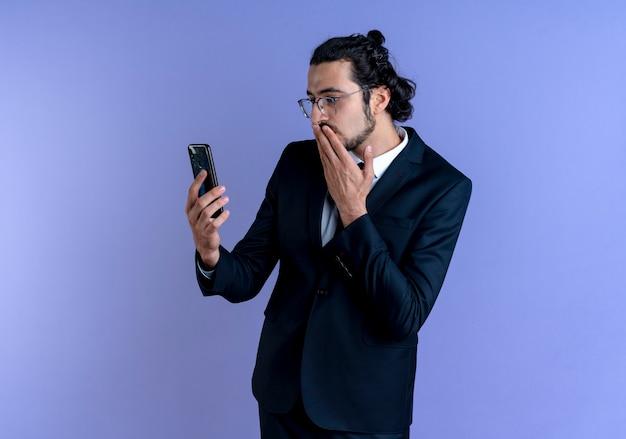 Uomo d'affari in abito nero e occhiali guardando lo schermo del suo smartphone sorpreso e confuso in piedi sopra la parete blu