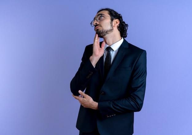 Uomo d'affari in abito nero e occhiali cercando di pensare perplesso in piedi sopra la parete blu