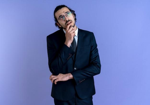 Uomo d'affari in abito nero e occhiali che osserva in su con la mano sul mento perplesso in piedi sopra la parete blu