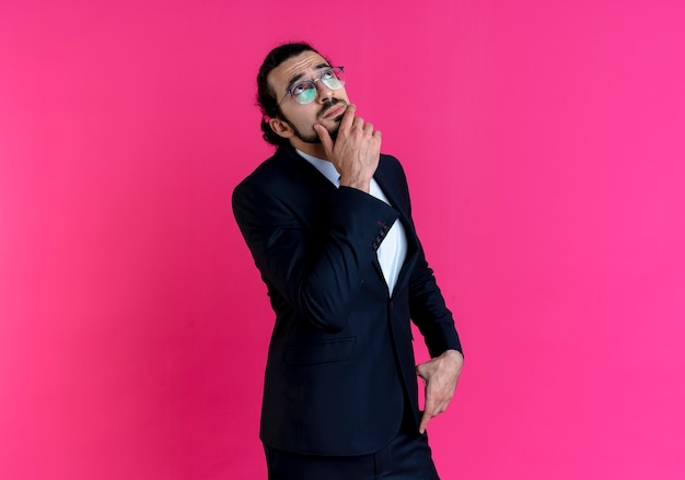 Uomo d'affari in abito nero e occhiali, alzando lo sguardo con la mano sul mento perplesso in piedi sopra il muro rosa