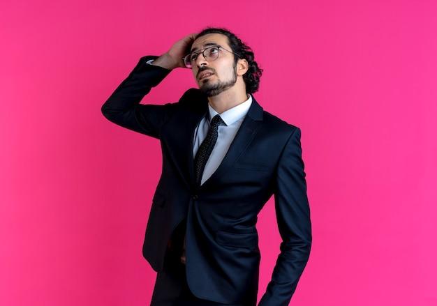 Uomo d'affari in abito nero e occhiali guardando con la mano sulla testa perplesso in piedi sopra il muro rosa