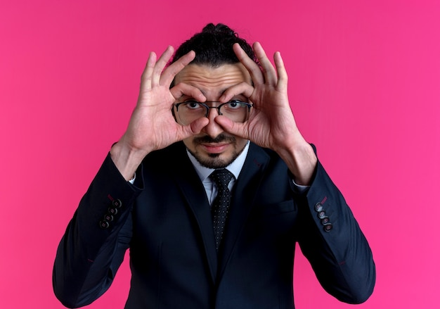 Business man in black suit and glasses making binocular gesture with fingers looking through fingers standing over pink wall