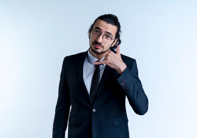 Uomo d'affari in abito nero e occhiali che mi fanno chiamare gesto con la mano in piedi sul muro bianco